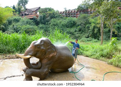 CHIANG RAI, THAILAND - JANUARY 8, 2017: A Mahout washing his elephant at the Anantara Golden Triangle Elephant Camp, a charity designed to help elephants and their handlers.