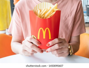 Chiang Rai, Thailand : July-12-2019 : Cropped shot of young woman holding french fries in McDonald's restaurant.