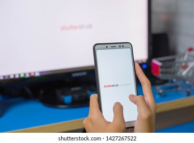 CHIANG RAI THAILAND - JUN 11 2019: Close Up to Female Hands Holding Smartphone Using Shutterstock Contributor Application on the Screen.