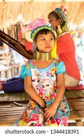 CHIANG RAI, THAILAND - MARCH 29, 2018: Portrait of a long neck little girl in a village near Chiang Rai, Thailand in a summer day