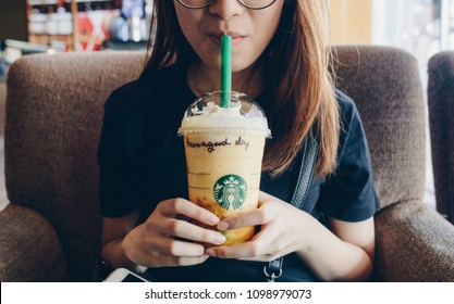 Chiang Rai, Thailand : May-23-2018 : Asian girl drinking Starbucks mango fruit jelly yogurt frappuccino in Starbucks coffee shop. (This menu is limited only in Southeast Asia)