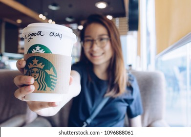 Chiang Rai, Thailand : May-23-2018 : Happy Asian girl showing a cup of Starbucks coffee in Starbucks coffee store.