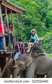 CHIANG RAI, THAILAND - September 28 : Tourists riding on the elephant across Kok river on September 28, 2013 in Chiang Rai, Thailand. Kok river is one of the most popular rivers for travel.