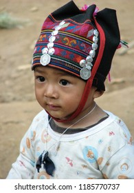 CHIANG RAI, THAILAND-JAN. 12, 2010:  In the hills outside the city, a child of the Akha ethnic minority wears traditional headgear while meeting visiting tourists.