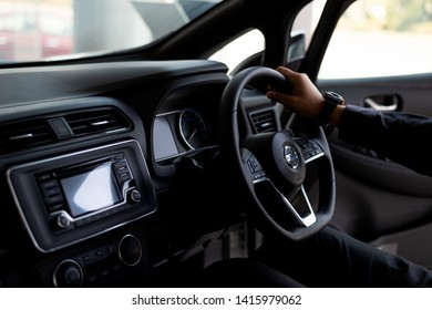 CHIANG RAI, THAILAND-MAY 04, 2019, Closeup Hand Of a Man Driving a All New Nissan Leaf EV Car Zero Emission With Soft-Focus And Over Light In The Background