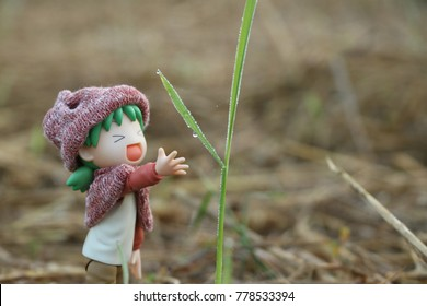 CHIANG RAI,THAILAND-December 13,2017:Miniature Yotsuba figure, Girl smiled cheerfully,Reaching hand for dew on the grass, It is a sign that Chiang Rai is cold.It's famous Japanese comedy comic series.