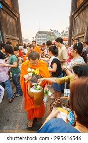 CHIANGMAI - APRIL 13, 2008: Songkran Festival, People put food offerings in a Buddhist monk's alms bowl for virtue at Tha Phae gate . Chiangmai, Thailand