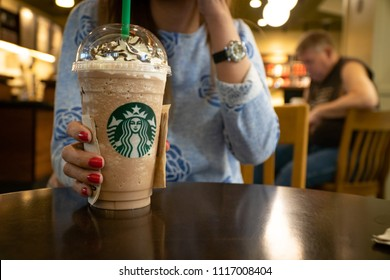 Chiangmai, Thailand - 25 April 2018: Woman holding Frapuccino in Starbucks coffee shop