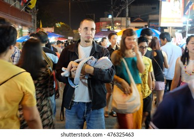 CHIANGMAI, THAILAND, 5 APRIL 2014 - A man is bringing a newborn baby to the public place. Crowded people in the night market.