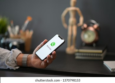 CHIANGMAI, THAILAND - APRIL 16, 2019 : Male hand holding WhatsApp mobile application on APPLE iPhone X screen shot