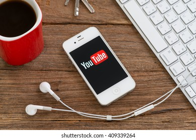 CHIANGMAI, THAILAND -APRIL 22, 2016:Brand Apple iPhone 4s with YouTube app on the screen lying on desk with headphones. YouTube is the popular online video-sharing website,