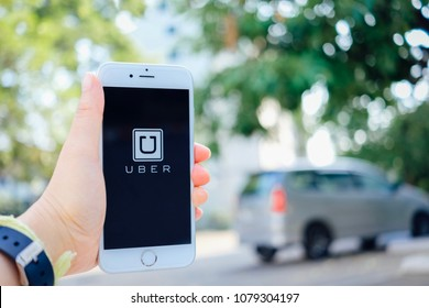 Chiangmai, Thailand - April 29, 2018 : hand holding iPhone6s and using Uber app on road with car parked, Uber is smartphone app based transportation network .