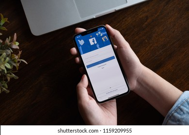 CHIANGMAI, THAILAND - AUG 18,2018 : A woman holding a iPhone X with social Internet service Facebook on the screen.