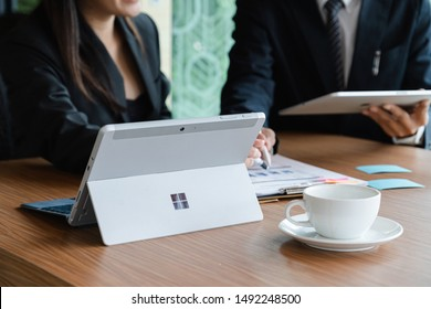CHIANGMAI, THAILAND - AUG 31, 2019 : Microsoft Surface tablet on desk with businesman and businesswoman discussing background. created by Microsoft for Windows 10.
