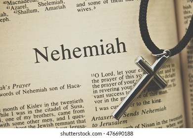 """CHIANGMAI, THAILAND, August 31,2016. Reading The New International Version of the Holy Bible on the book of """" nehemiah """" with the holy cross on table at home"""