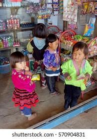 CHIANGMAI Thailand - DEC 25, 2016: Happy Unidentified Hmong (Miao) childrens wearing Hmong dress and buy snacks in mini shop at khunchangkain Mong Village.