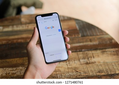 CHIANGMAI, THAILAND - DEC 30,2018 : close up on man finger hold smartphone iphone X for searching on www.google.com, iPhone X was created and developed by the Apple in