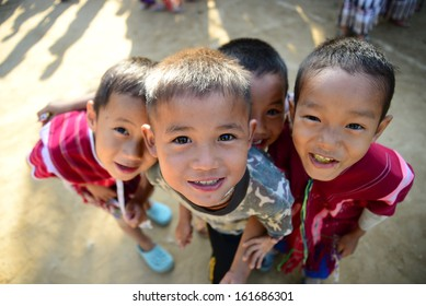 CHIANGMAI, THAILAND - December 15, 2012: A group of unidentified street children dressed in tribe costumes welcoming tourists as they pass through their village.