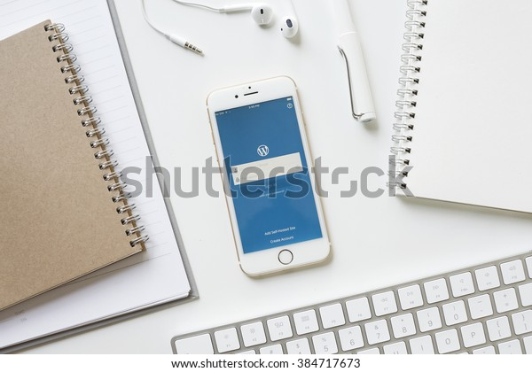 CHIANGMAI, THAILAND - FEB 15, 2016: Apple iPhone 6s showing service WordPress screen iOS app on office table with school supplies. WordPress is a free and open-source blogging tool