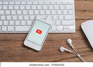 CHIANGMAI, THAILAND - February 10, 2016 :Selective focus Brand Apple iPhone 4s with YouTube app on the screen lying on desk with headphones. YouTube is the popular online video-sharing website,
