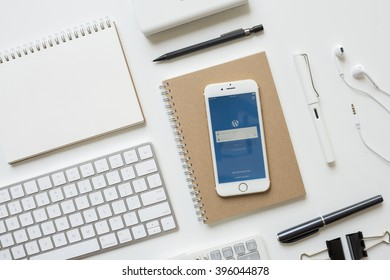 CHIANGMAI, THAILAND - FEBRUARY 16, 2016: Apple iPhone 6s White Gold display WordPress app iOS on office table with supplies. WordPress is a free and open-source content management system