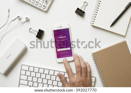 CHIANGMAI, THAILAND - FEBRUARY 16, 2016: Man hand touching on Apple iPhone 6s button and open Instagram iOS app on office desk. Instagram is photo-sharing social network.