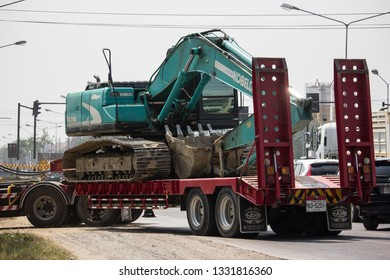 Chiangmai, Thailand - February 18 2019: Trailer Truck and Backhoe  of Payawan Transport Company. Photo at road no.121 about 8 km from downtown Chiangmai, thailand.