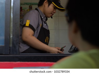CHIANGMAI, THAILAND - February 25, 2018;  A drive-thru customer is paying to a McDonald's employee through the window without leaving her car