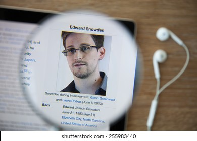 CHIANGMAI, THAILAND - February 26, 2015: Photo of Wikipedia article page about Edward Snowden on a ipad monitor screen through a magnifying glass.