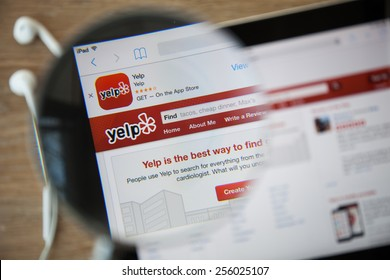 CHIANGMAI, THAILAND - February 26, 2015: Photo of Yelp homepage on a ipad monitor screen through a magnifying glass.
