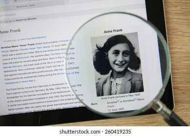 CHIANGMAI, THAILAND - February 26, 2015: Photo of Wikipedia article page about Anne Frank on a ipad monitor screen through a magnifying glass.