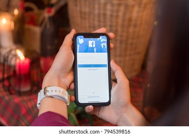 CHIANGMAI, THAILAND - JAN 16,2018:Brand new Apple iphone X hand is pressing the Facebook ,Social media are using for information sharing and networking.