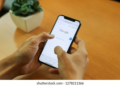 CHIANGMAI, THAILAND - JAN 8,2019 : close up on Man finger hold smartphone iphone X for searching on www.google.com, iPhone X was created and developed by the Apple inc.