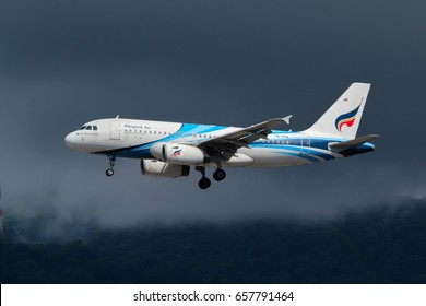 Chiangmai, Thailand. July 9, 2016. Bangkok Airways Airbus A319-100 Reg. HS-PPA on Short Final for Landing at Chiangmai International Airport with Rain Cloud and Mountain Background