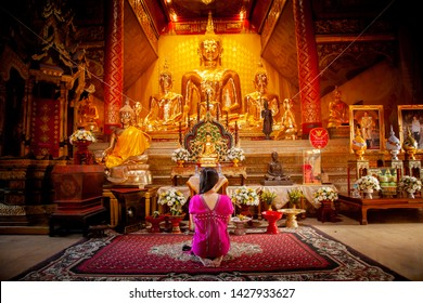 Chiangmai, Thailand- June 3, 2019 : Asia woman wearing traditional dress of Thailand Pay respect to big golden buddha statute in the Silver temple Sanctuary Wat Srisuphan Chiangmai. Worship pray