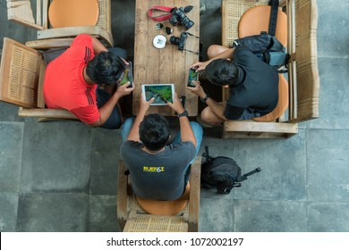 Chiangmai, Thailand - MARCH 25, 2018 : Top view of Undefined men using the ipad and iphone playing the Garena RoV Mobile Game online at coffee shop on 25 March, 2018 in chiang mai province, Thailand