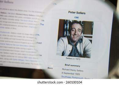 CHIANGMAI, THAILAND - March 5, 2015: Photo of Wikipedia article page about Peter Sellers on a ipad monitor screen through a magnifying glass.