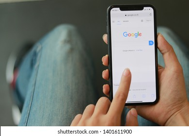 CHIANGMAI, THAILAND - May 17,2019 : close up on woman hand hold iphone XS for searching on www.google.com, iPhone XS was created and developed by the Apple inc