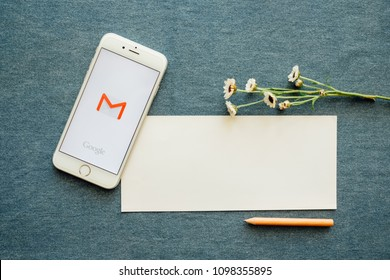 Chiangmai, Thailand - May 25, 2018: Screen short of Gmail app showing on iPhone6s. Gmail is free e-mail service provided by Google. And white note paper, pencil and flowers background.