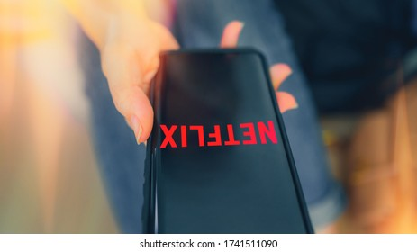 Chiangmai, Thailand - May 26, 2020 : women use Netflix app on smart phone screen. Netflix is an international leading subscription service for watching TV episodes and movies on mobile