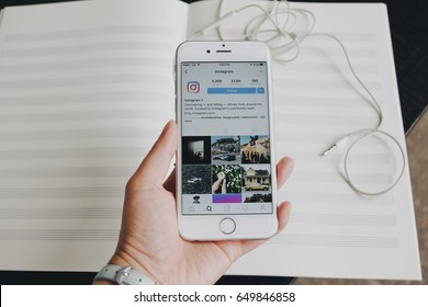 Chiangmai, Thailand - May 30, 2017: hand holding Apple iPhone6 with Instagram application on the screen. Instagram is photo - sharing app for smartphone. With piano book blurred background.