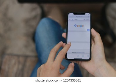 CHIANGMAI, THAILAND - NOV 15,2018 : close up on lady finger hold smartphone iphone X for searching on www.google.com, iPhone X was created and developed by the Apple inc.