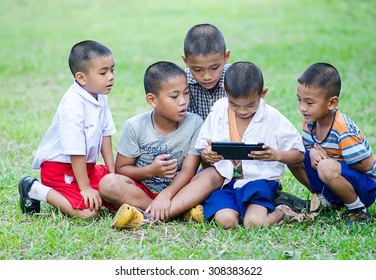 CHIANGMAI, THAILAND - NOVEMBER 12, 2014: Unidentified Lisu ethnic children are playing with digital tablet in the park on November 12 , 2014 at Chiang dao ,Chiangmai,Thailand