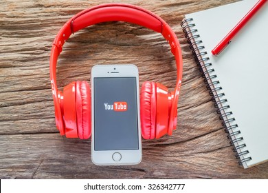 CHIANGMAI, THAILAND -OCTOBER 12, 2015:Brand new Apple iPhone with YouTube app on the screen lying on desk with headphones.