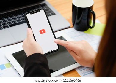 CHIANGMAI,THAILAND 2 JULY 2018 : A man showing screen shot of Youtube on new iphone x. YouTube app on the screen lying on old wood desk. YouTube is the popular online video sharing website.