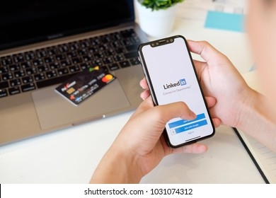 CHIANGMAI,THAILAND 22 FEB 2018 : Man holding New iPhone X on hand open LinkedIn application on the screen. LinkedIn is a business-oriented social networking service.