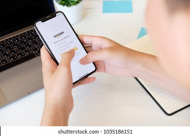 CHIANGMAI,THAILAND 22 FEB 2018 : Man holding New iPhone X on hand open mazon application,Amazon is an American international electronic commerce company.