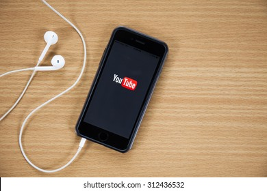 CHIANGMAI,THAILAND - AUGUST 31, 2015:Brand new Apple iPhone 5 with YouTube app on the screen lying on desk with headphones. YouTube is the popular online video-sharing website.