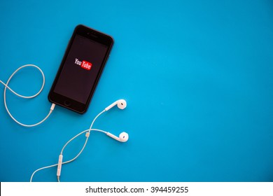 CHIANGMAI,THAILAND - MARCH 22, 2016:Brand new Apple iPhone 6 with YouTube app on the screen lying on desk with headphones. YouTube is the popular online video-sharing website,