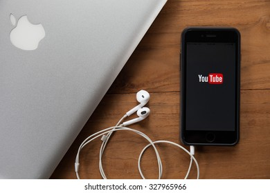 CHIANGMAI,THAILAND - OCTOBER 10, 2015:Brand new Apple iPhone 6 with YouTube app on the screen lying on desk with headphones. YouTube is the popular online video-sharing website,